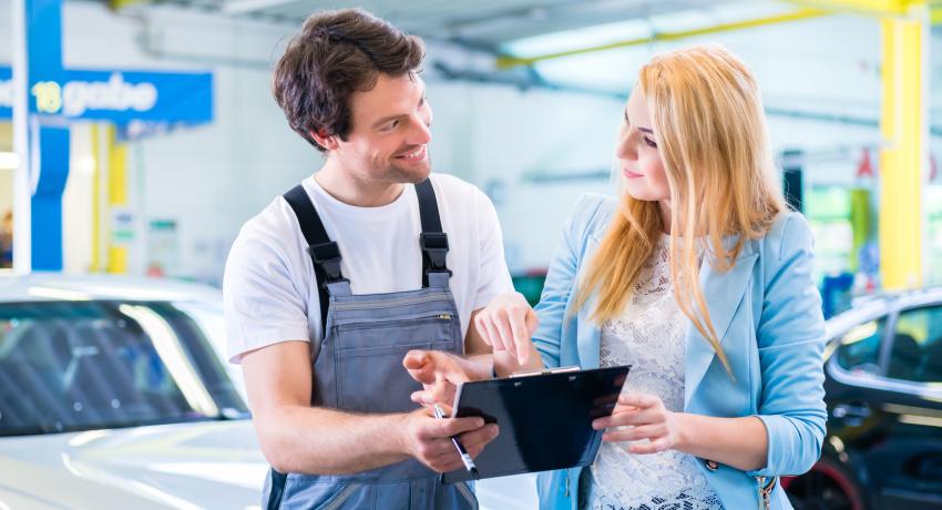 Workshop mechanic handing over car to client